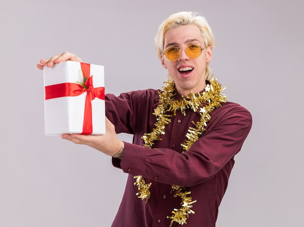 Joyful young blonde man wearing glasses with tinsel garland around neck stretching out gift package towards camera looking at camera isolated on white background