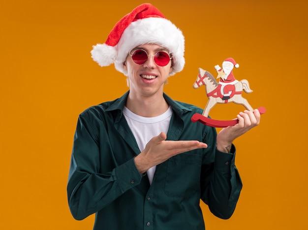 オレンジ色の背景に分離されたカメラを見て揺れる馬の置物にサンタを手で持って指さし、サンタの帽子とメガネを身に着けているうれしそうな若いブロンドの男