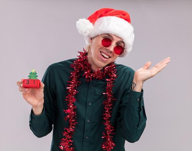 白い背景で隔離の空の手を示すカメラを見て日付とクリスマスツリーのおもちゃを保持している首の周りに見掛け倒しの花輪とサンタの帽子とメガネを身に着けているうれしそうな若いブロンドの男
