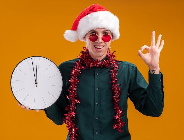 オレンジ色の背景に分離されたokサインをしているカメラを見て時計を保持している首の周りに見掛け倒しの花輪とサンタの帽子と眼鏡を身に着けているうれしそうな若いブロンドの男