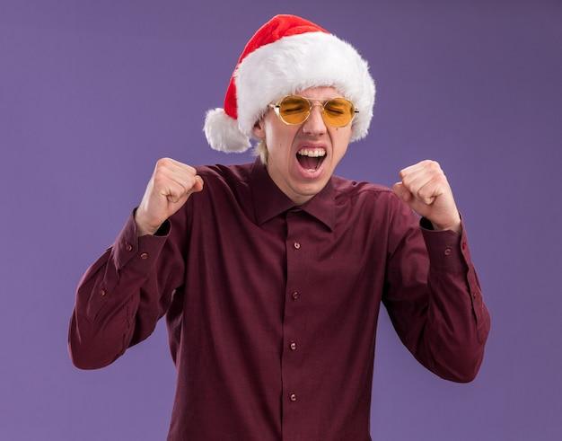 Gioioso giovane uomo biondo che indossa santa cappello e occhiali facendo sì gesto con gli occhi chiusi isolati sulla parete viola