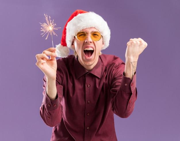 Gioioso giovane uomo biondo che indossa il cappello della santa e occhiali che tengono la scintilla festiva facendo sì gesto isolato sulla parete viola