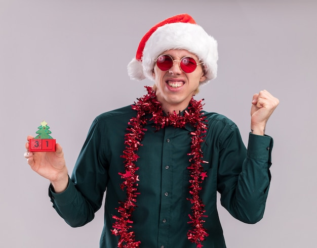 Joyful young blonde man wearing santa hat and glasses with tinsel garland around neck holding christmas tree toy with date looking at camera doing yes gesture winking isolated on white background