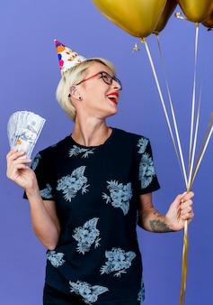 紫色の背景で隔離の側を見て風船とお金を保持している眼鏡と誕生日の帽子を身に着けているうれしそうな若いブロンドのパーティーの女の子