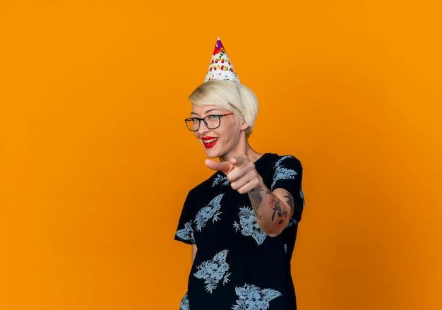 コピースペースでオレンジ色の背景に分離されたカメラを見て、指している眼鏡と誕生日の帽子を身に着けているうれしそうな若いブロンドのパーティーの女の子