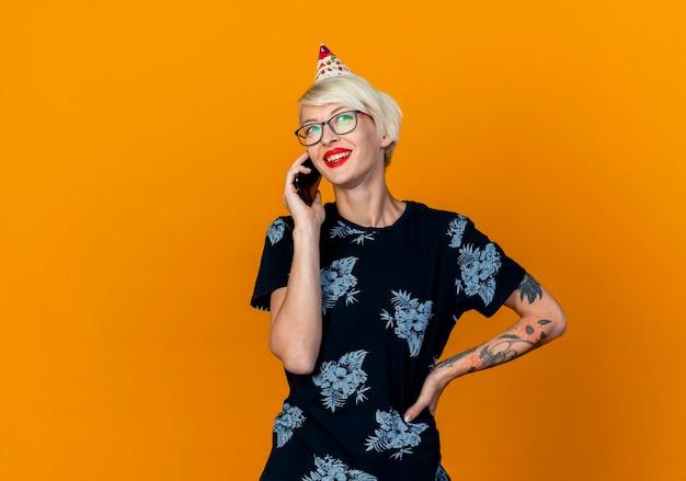 コピースペースでオレンジ色の背景に分離された側を見て腰に手を保ちながら電話で話している眼鏡と誕生日の帽子を身に着けているうれしそうな若いブロンドのパーティーの女の子