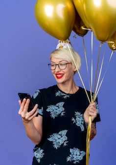 Joyful young blonde party girl wearing glasses and birthday cap holding balloons and mobile phone looking at phone isolated on purple background
