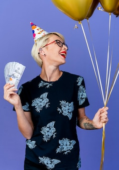 Joyful young blonde party girl wearing glasses and birthday cap holding balloons and money looking at side isolated on purple background