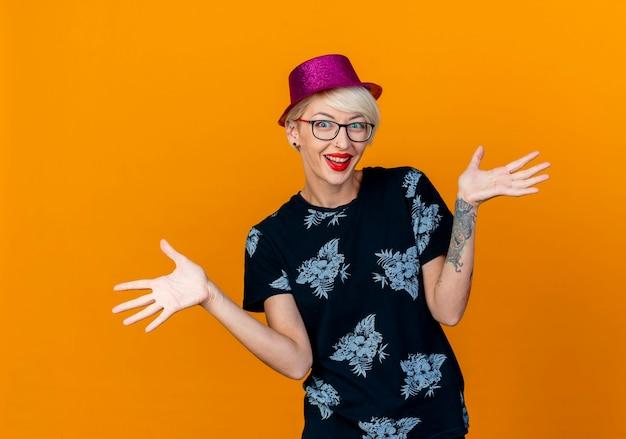 オレンジ色の背景で隔離の空の手を示すカメラを見てパーティー帽子をかぶってうれしそうな若いブロンドのパーティーの女の子