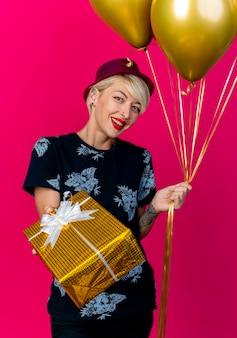 Gioiosa ragazza bionda giovane festa indossando il cappello del partito che allunga la confezione regalo e che tiene palloncini guardando la telecamera isolata su sfondo cremisi