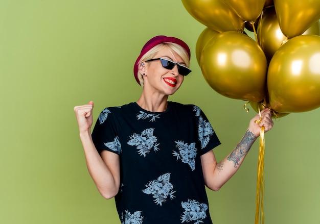 Gioiosa giovane ragazza bionda festa indossando cappello da festa e occhiali da sole che tengono palloncini facendo sì gesto isolato su sfondo verde oliva