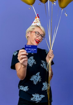 紫色の壁で隔離の正面でウィンクする風船とクレジットカードを保持している眼鏡と誕生日の帽子を身に着けているうれしそうな若いブロンドのパーティーの女性