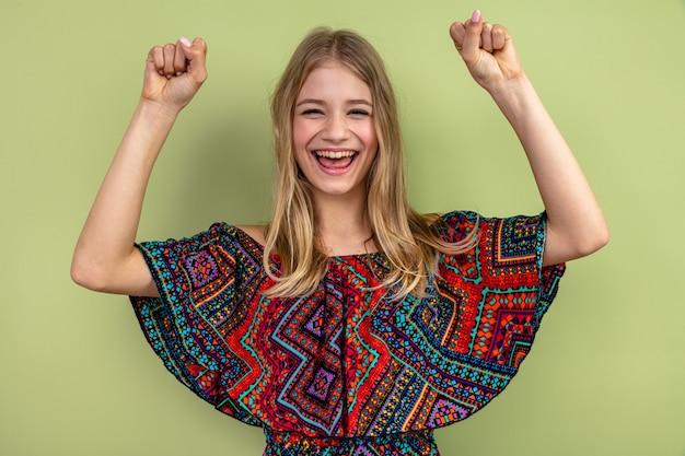 Gioiosa giovane ragazza slava bionda in piedi con i pugni alzati