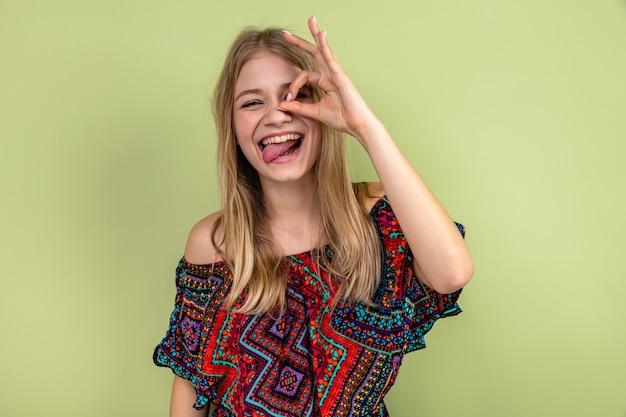 Радостная молодая блондинка славянская девушка высунула язык и смотрит вперед сквозь пальцы