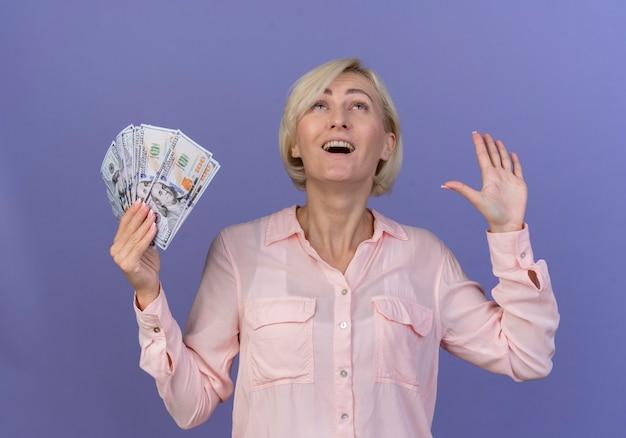 Gioiosa giovane bionda donna slava che osserva in su tenendo i soldi e mostrando la mano vuota isolata su sfondo viola