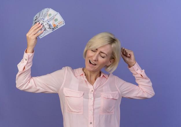 Gioiosa giovane bionda donna slava alzando i soldi stringendo il pugno con gli occhi chiusi isolati su sfondo viola