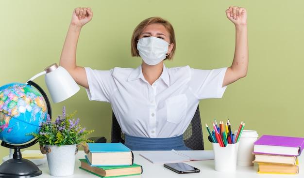 Gioiosa giovane studentessa bionda che indossa una maschera protettiva seduta alla scrivania con gli strumenti della scuola che guarda l'obbiettivo facendo sì gesto isolato sul muro verde oliva