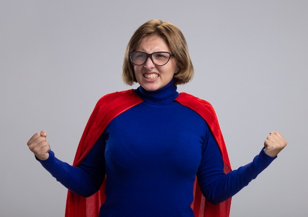 Радостная молодая блондинка супергероя девушка в красном плаще в очках смотрит в сторону, делая жест да, изолированные на белом фоне