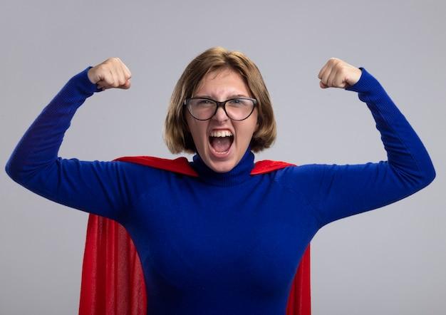 Gioiosa giovane ragazza bionda del supereroe in mantello rosso con gli occhiali che guarda l'obbiettivo facendo forte gesto godendo della vittoria isolato su sfondo bianco