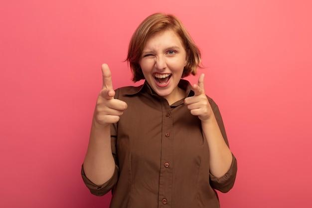 コピースペースでピンクの壁に分離されたジェスチャーをしているフロントウィンクを見てうれしそうな若いブロンドの女性