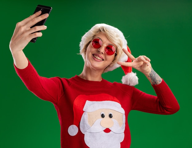 クリスマスの帽子とサンタクロースのクリスマスセーターを身に着けているうれしそうな若いブロンドの女性は、緑の背景に分離されたselfieを取っているピースサインをしている眼鏡