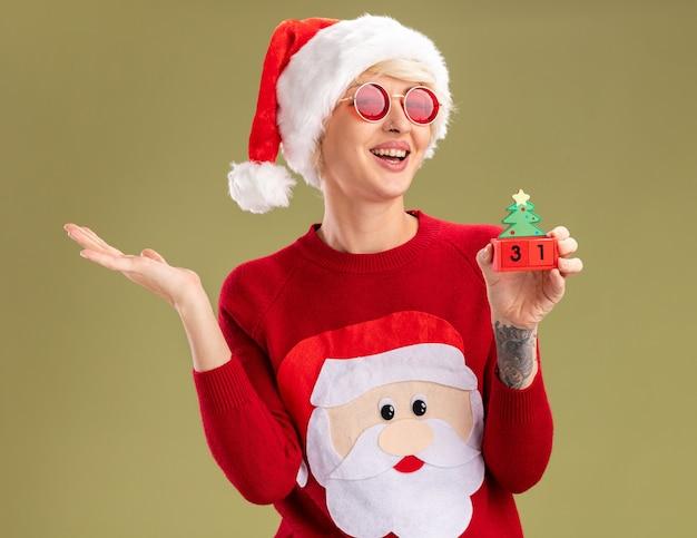 クリスマス帽子とサンタ クロース クリスマス セーターを着て、オリーブ グリーンの壁に孤立した空の手を示す日付でクリスマス ツリーのおもちゃを保持しているうれしそうな若いブロンドの女性