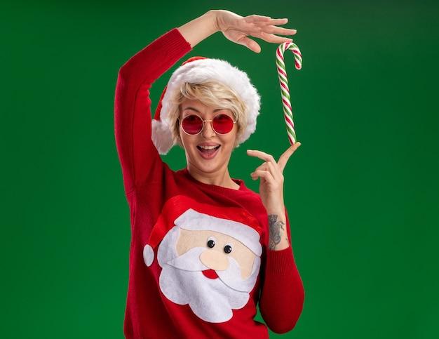 緑の背景で隔離の頭の近くにクリスマスキャンディケインを保持しているカメラを見てメガネとクリスマス帽子とサンタクロースのクリスマスセーターを身に着けているうれしそうな若いブロンドの女性