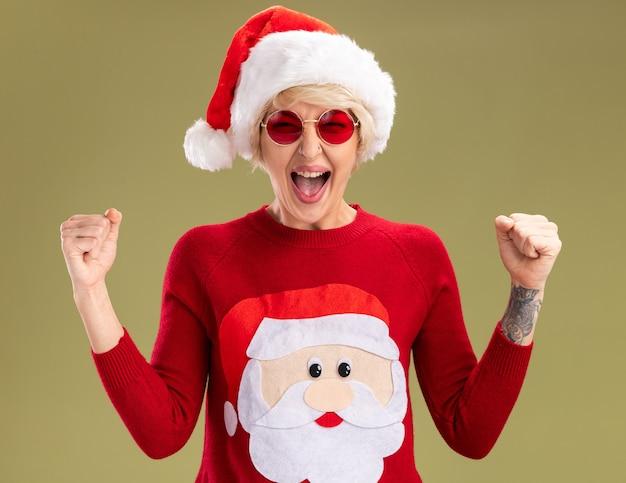 Радостная молодая блондинка в рождественской шапке и рождественском свитере санта-клауса в очках, глядя, делая жест да, изолированные на оливково-зеленой стене