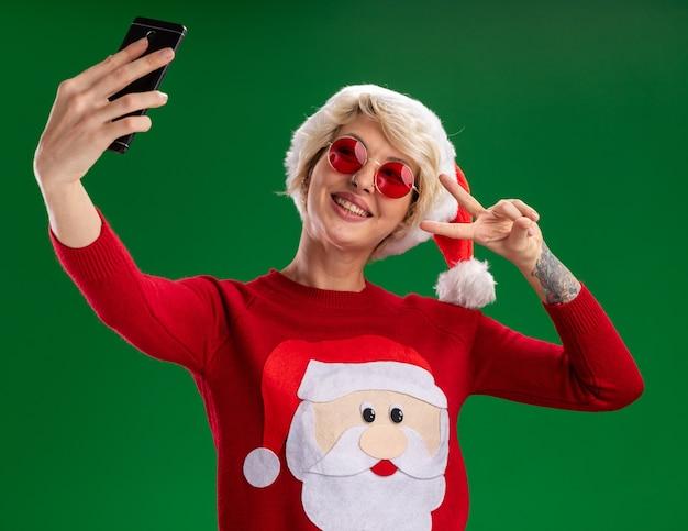 Gioiosa giovane donna bionda che indossa il cappello di natale e babbo natale maglione di natale con gli occhiali facendo segno di pace tenendo selfie isolato su sfondo verde