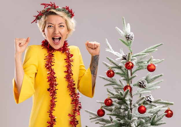 Радостная молодая блондинка в рождественском венке и гирлянде из мишуры на шее, стоящая возле украшенной рождественской елки, глядя, делает жест да, изолированные на белой стене