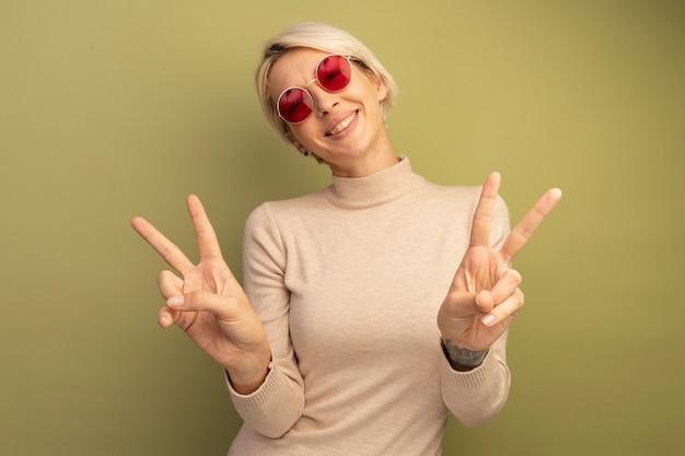オリーブグリーンの壁に分離されたピースサインをやって正面を見てサングラスをかけてうれしそうな若いブロンドの女性
