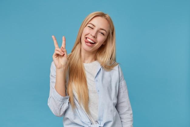 Gioiosa giovane donna bionda con i capelli lunghi ingannare in abiti casual, mostrando la lingua allegramente e alzando due dita con gesto di vittoria