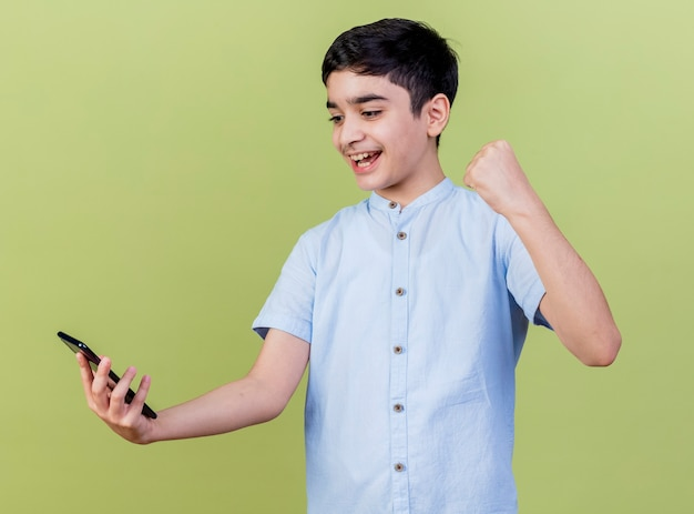 Joyful young boy holding and looking at mobile phone doing yes gesture isolated on olive green wall