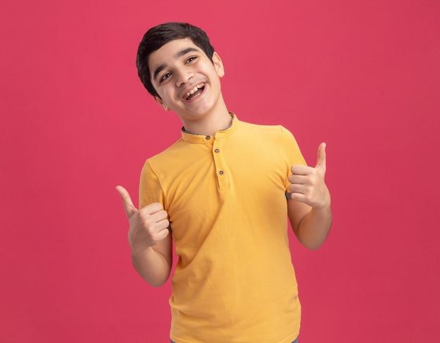 ピンクの壁に分離された親指を上に表示している側を見てうれしそうな少年