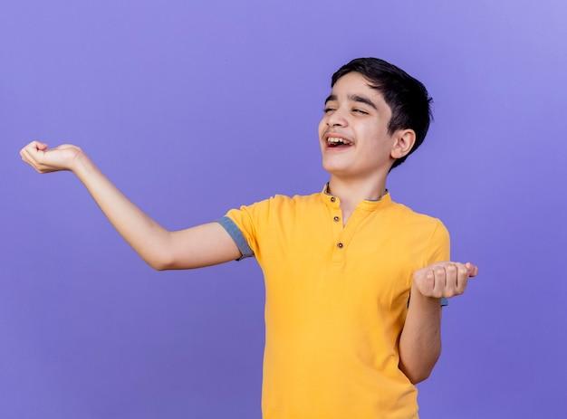 보라색 벽에 고립 된 손을 뻗어 측면을보고 즐거운 어린 소년
