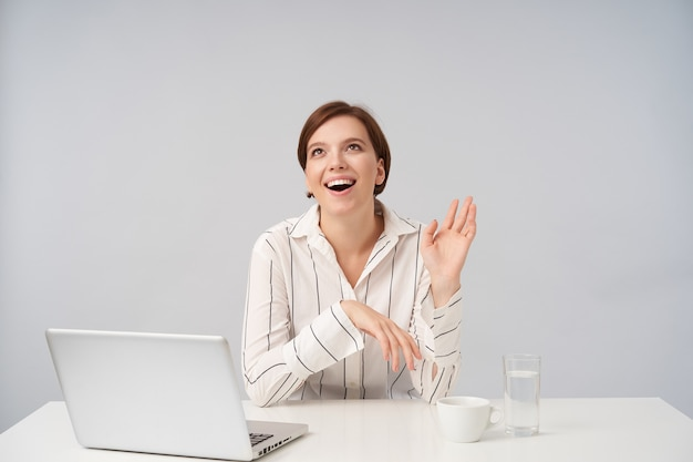 Gioiosa giovane donna dai capelli castani con taglio di capelli corto alla moda che tiene il palmo sollevato mentre guarda felicemente verso l'alto, vestita con camicia a righe mentre è seduto su bianco