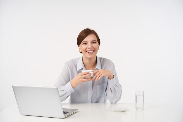 Gioiosa giovane donna dai capelli castani con acconciatura casual che ride felicemente mentre beve il caffè durante la giornata lavorativa, vestita in camicia blu mentre posa su bianco