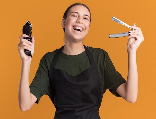 Радостная молодая брюнетка-парикмахер в униформе с машинкой для стрижки волос и опасной бритвой