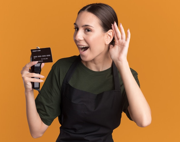 La gioiosa giovane barbiere bruna in uniforme tiene il tagliacapelli e la carta di credito tenendo la mano dietro l'orecchio