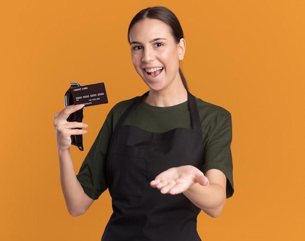 Gioiosa giovane barbiere bruna in uniforme tiene le tosatrici e una carta di credito che punta alla telecamera con la mano