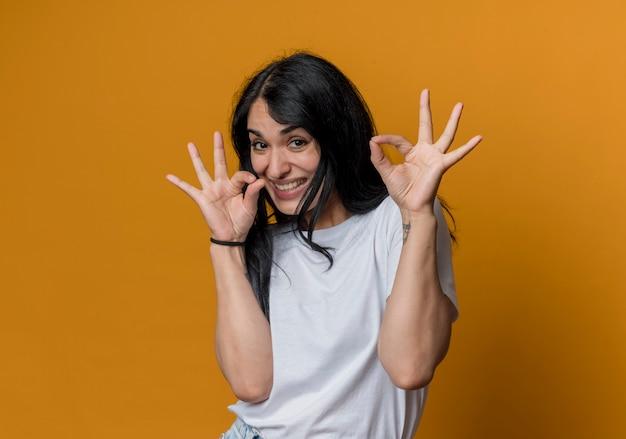 즐거운 젊은 갈색 머리 백인 여자 제스처 오렌지 벽에 고립 된 두 손으로 확인 손 기호
