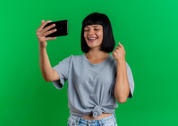 Gioiosa giovane ragazza caucasica bruna sta con gli occhi chiusi mantenendo il pugno e tenendo il telefono isolato su sfondo verde con copia spazio