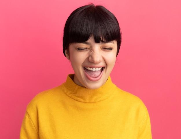 Радостная молодая брюнетка кавказская девушка стоит с закрытыми глазами
