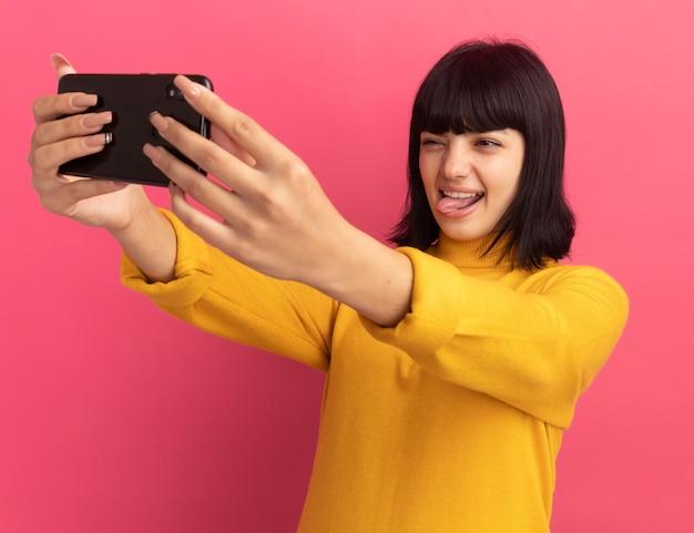 Радостная молодая кавказская девушка брюнетка высунула язык и смотрит на телефон на розовом