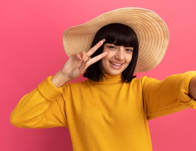 Gioiosa giovane ragazza caucasica bruna che indossa il cappello da spiaggia gesti vittoria segno della mano che tiene la macchina fotografica prendendo selfie isolato sulla parete rosa con copia spazio