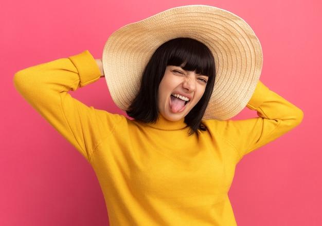 Радостная молодая кавказская девушка брюнетка в пляжной шляпе высунула язык и держится за голову на розовом