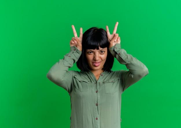 Gioiosa giovane donna caucasica bruna mette le mani sulla testa gesticolando corna e tira fuori la lingua isolata su sfondo verde con spazio di copia