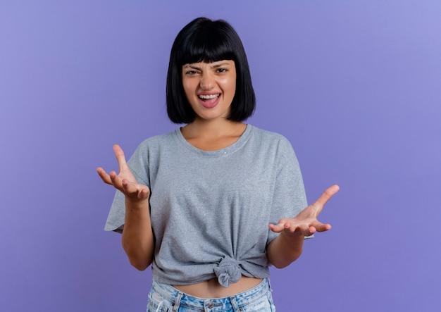 Gioiosa giovane donna caucasica bruna sta con le mani aperte che guarda l'obbiettivo isolato su sfondo viola con spazio di copia