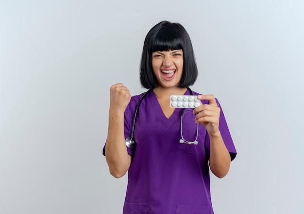 Il giovane medico femminile del brunette allegro in uniforme con lo stetoscopio tiene il pugno e tiene la medicina
