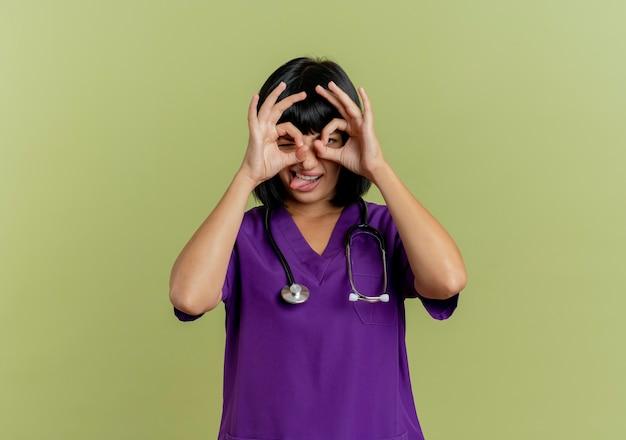 Gioiosa giovane dottoressa bruna in uniforme con lo stetoscopio sporge la lingua guardando attraverso le dita isolate su sfondo verde oliva con spazio di copia